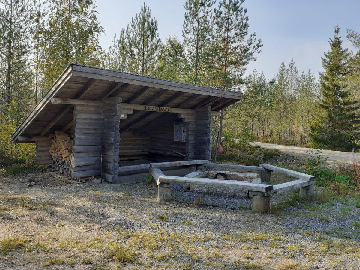 Sivin laavun edessä on iso kivinen nuotiorinki ja sen ympärillä istumapaikat, laavun sivulla polttopuita ja palosanko.