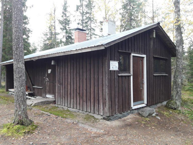Äystön metsäkämppä on ruskea, matala rakennus. Seinällä kyltti ja räystään alla on linnunpönttö.