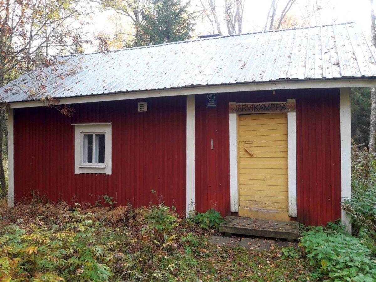 Järvikämpän pieni punainen pirtti edestä päin kuvattuna, kuvassa keltainen ovi jonka yläpuolella nimikyltti. Syksyllä otettu valokuva, peltikatolla puunlehtiä, ruskan värejä kasveissa.