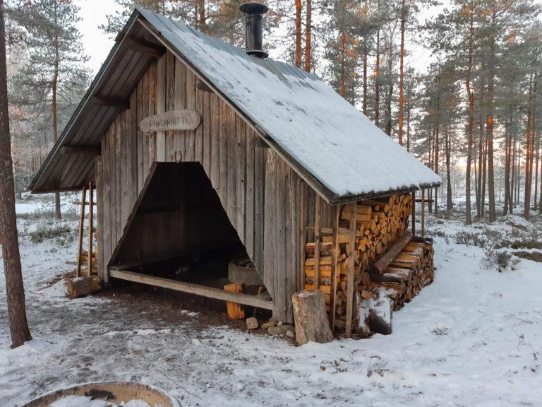 Lumisessa mäntymetsässä oleva puinen laavu kuvattu etuviistoon, laavun seinän vierustalla on polttopuita ja oviaukon yläpuolella puinen kyltti, jossa lukee Pintapirtti.