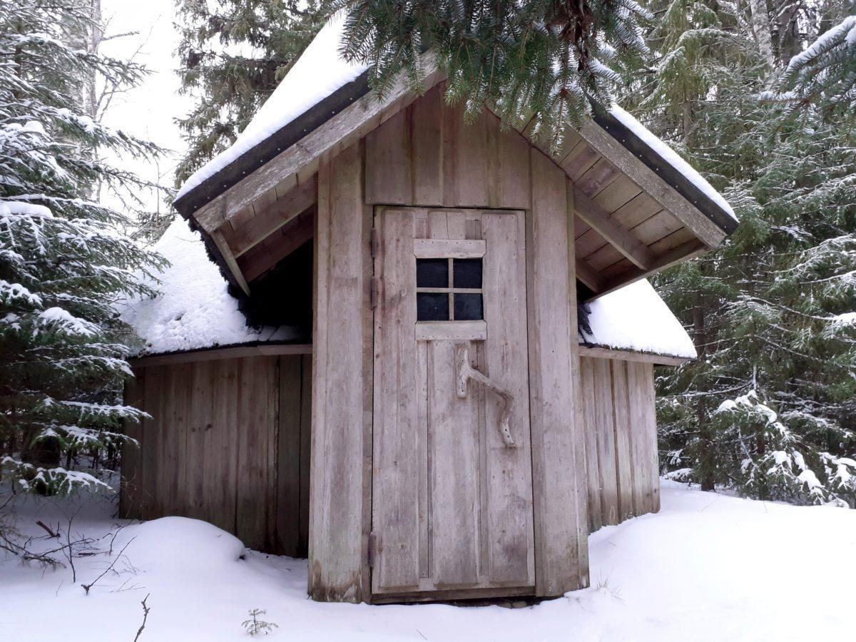 Kota kuvattu suoraan edestä päin, lunta kodan ympärillä olevilla kuusilla.