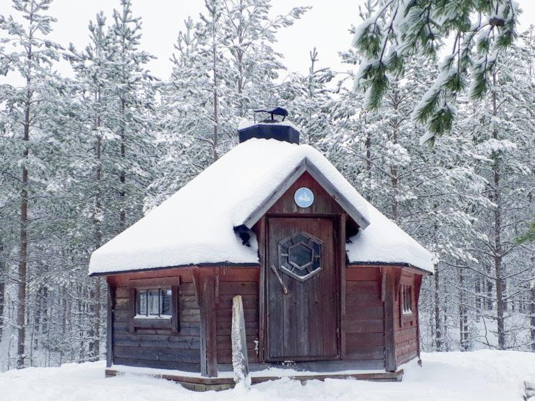 Talvisessa kuvassa hirsinen kota, oven yläpuolella moottorikelkan merkki.