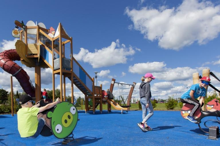 Kesäisessä kuvassa kolme lasta leikkimässä Angry Birds leikkipuistossa. Etualalla keinuja ja takana iso kiipeilykokonaisuus.