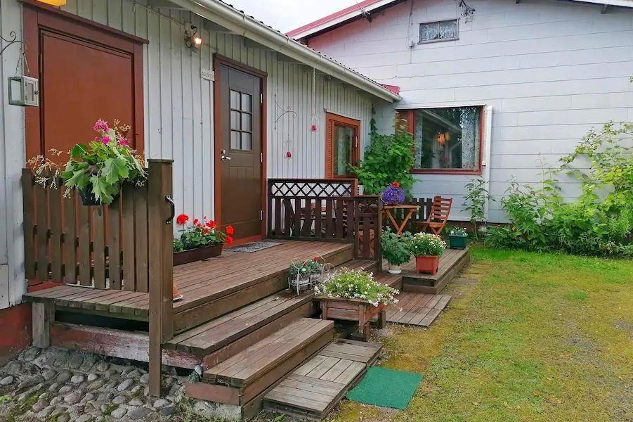 Kuvassa majatalon etupiha, etualalla portaat, joilla kukka-asetelmat.