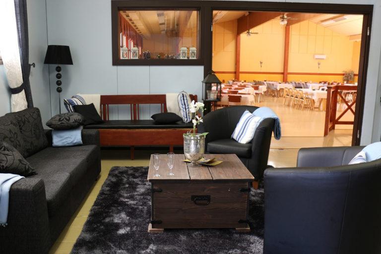 Oleskelutila kuvattuna, jossa sohvaryhmä. Taka-alalla juhlatila, jossa pöytiä.