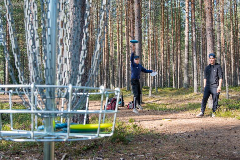 Etualalla metallinen frisbeegolgkori, jossa kiekkoja, kauempana kaksi henkilöä heittämässä kiekkoja.