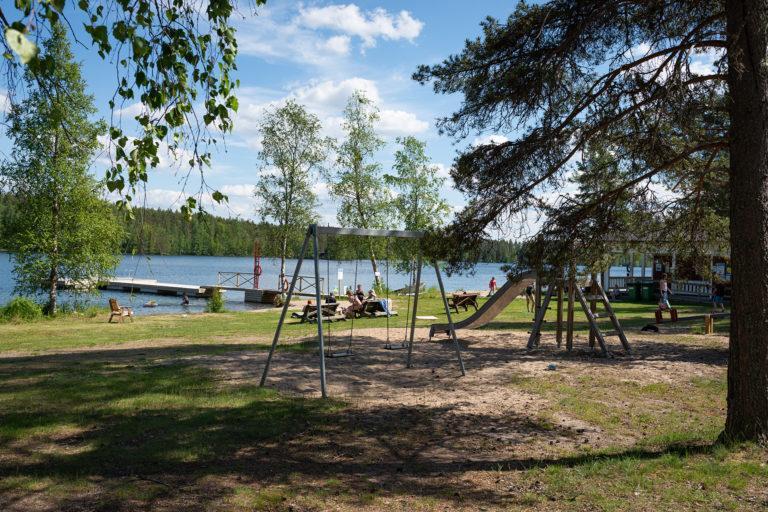 Kangasjärven rannalta löytyy leikkikenttä, kuvassa etualalla keinu oikealla liukumäki, taka-alalla siintää järvimaisema.