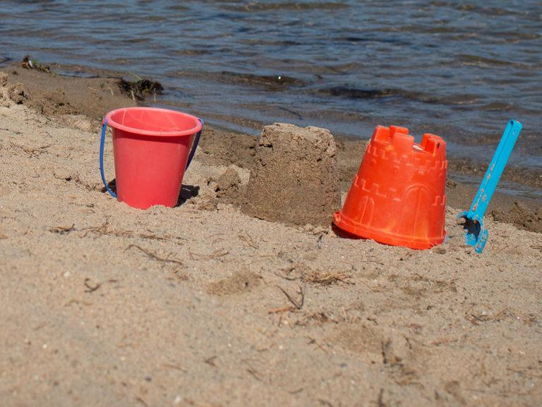 Kuvituskuva, hiekkaranta ja leikkivälineet.