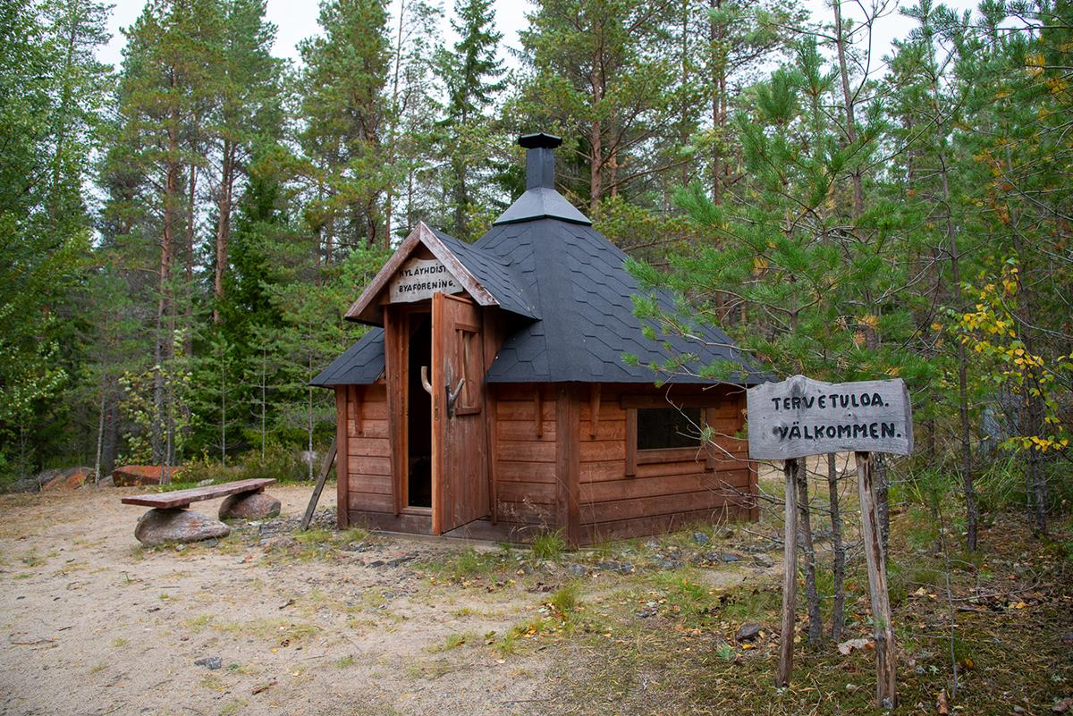 Kivipuiston kota edestä viistoon kuvattuna. Kuvassa tervetuloa kyltti oikealla, laavu keskellä ja penkki vasemalla, laavun takana on puita.