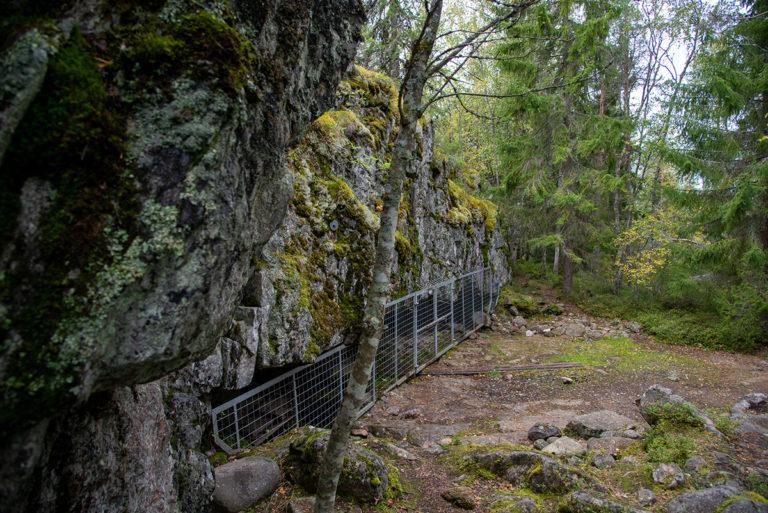 Korkean suoran kallioseinän alla on aidattu luola.