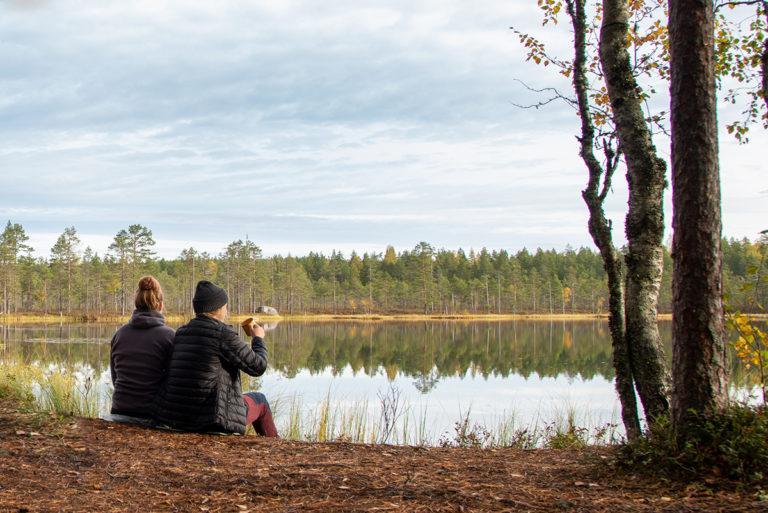 Kaksi ihmistä istuu Spitaalijärven rannalla ja katsoo järvelle päin.