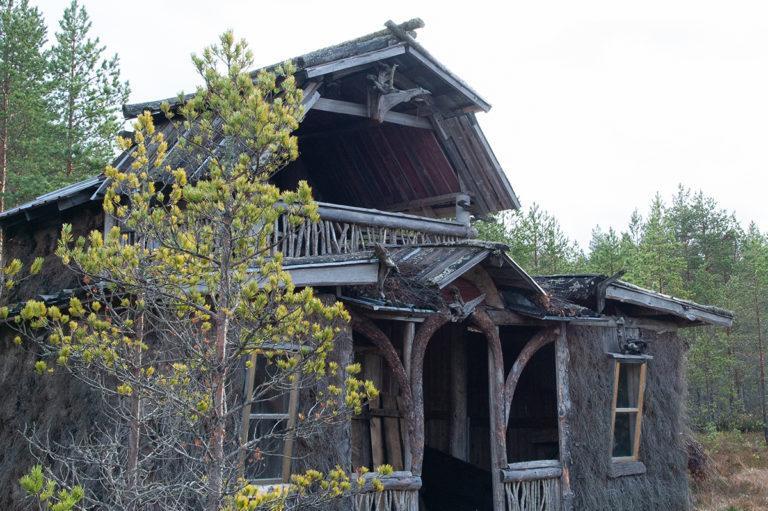Saunarakennus Ruuhinevan Kammikylässä. Kuvan rakennus kuvattu etuviistoon, etualalla pieni mänty. Rakennusmateriaaleina käytetty paljon luonnosta löytyviä materiaaleja.