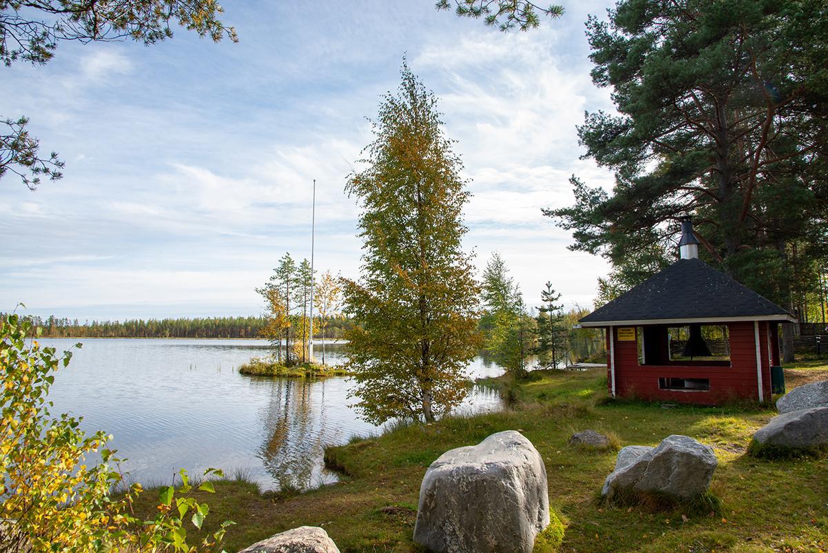 Hiukkajärven ranta ja grillikatos. Kuvassa etualalla isoja kiviä, punainen hirsinen grillirakennus, koivuja ja järvessä pieni saar, jossa lippumasto.