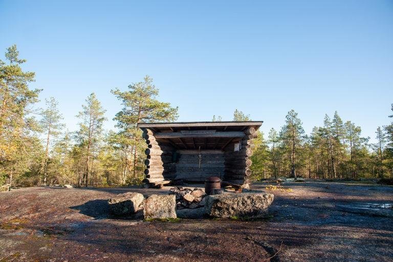 Hirsinen laavu sijaitsee Käräjävuorella kallioisella paikalla. Laavu kuvattu edestä, taustalla mäntyjä ja sininen taivas.