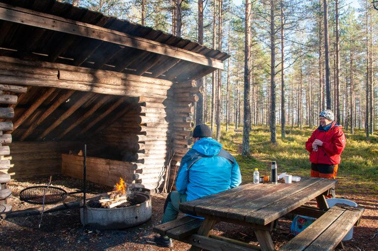 Pariskunta laavun edessä nauttimassa retkieväitä. Nuotio palaa, mies katsoo tulta ja nainen hymyilee.