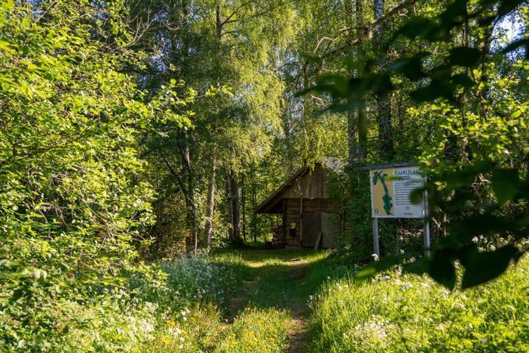 Kesäinen kuva, jossa näkyy taustalla vanha puinen rakennus ja valkoinen opastekyltti