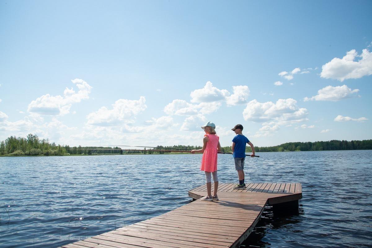Kesäisenä päivänä kaksi lasta puisellä laiturilla onkimassa kaloja.