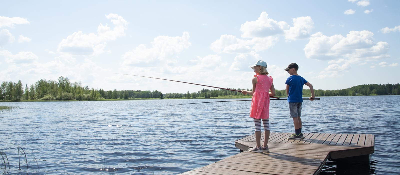 Poika ja tyttö laiturilla kalassa.