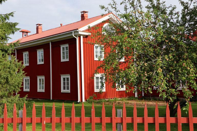 Punainen kaksikerroksinen rakennus, etualalla omenapuut ja punainen aita.
