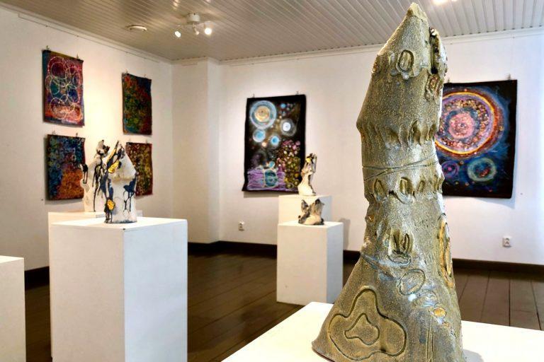 Sisätila taidegalleriasta, etualalla patsas, tak-alalla kaksi patsasta sekä taulut seinillä.