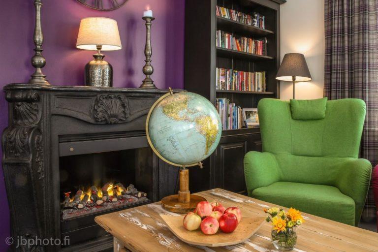 Kuva Hiljahelenan oleskelutilasta. Etualalla pöytä, jolla karttapallo, omenavati ja kukkamaljakko, taustalla kirjahylly, takka, lamppuja ja nojatuoli.