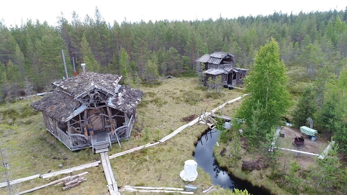 Ruuhinevalla sijaitsee lukuisia rakennuksia mm. kaksi saunaa. Ilmakuvassa kaksi pääosin luonnonmateriaalesta rakennettua saunarakennusta, suo, oja ja pitkospuut.