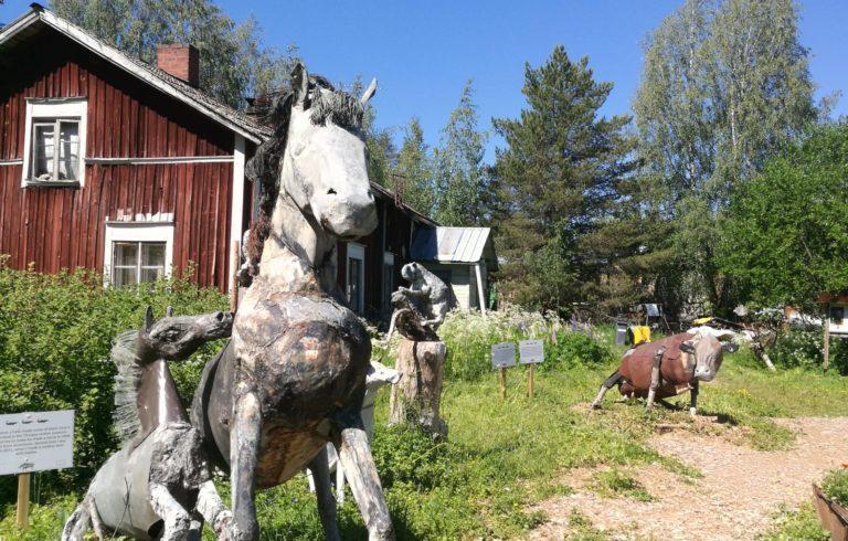 Etualalla kaksi pääosin metallista valmistettua hevoshahmoa, kauempana ruosteisen näköinen lehmähahmo, taustalla punainen rakennus.