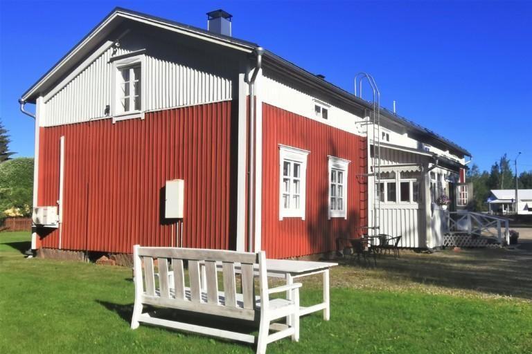 Punaninen puinen puolitoistakerroksinen talo, etualalla valkoinen penkki ja pöytä.
