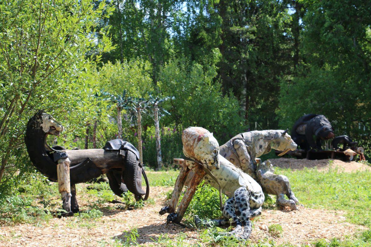 Kesäisessä kuvassa kierrätysmateriaaleista mm. metallista ja autonrenkaista tehtyjä eläinhahmoja, etualalla tiikereitä, taka-alalla karhuja sekä palmuja.