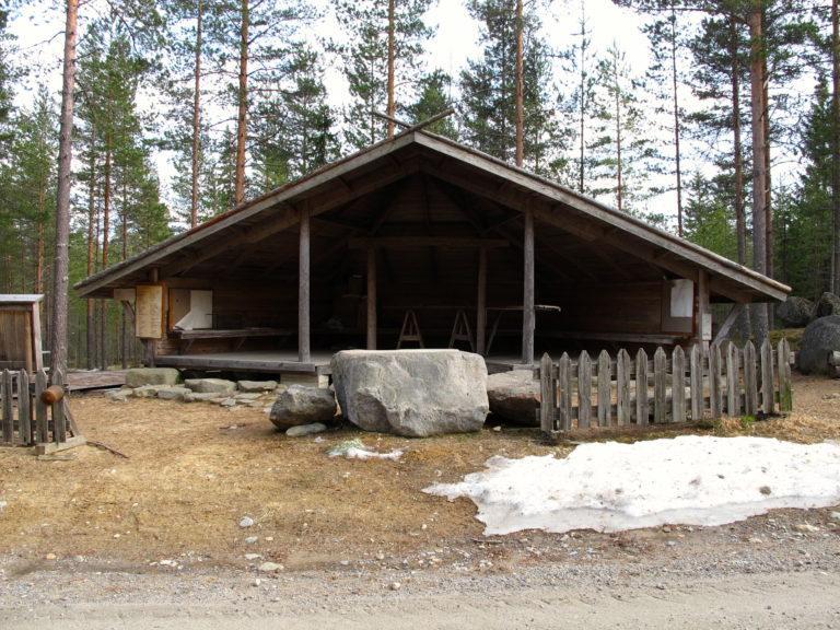 Iso puinen laavu edestä päin kuvattuna. Laavun edessä isompia kiviä sekä puinen aita ja pieni lumikasa.