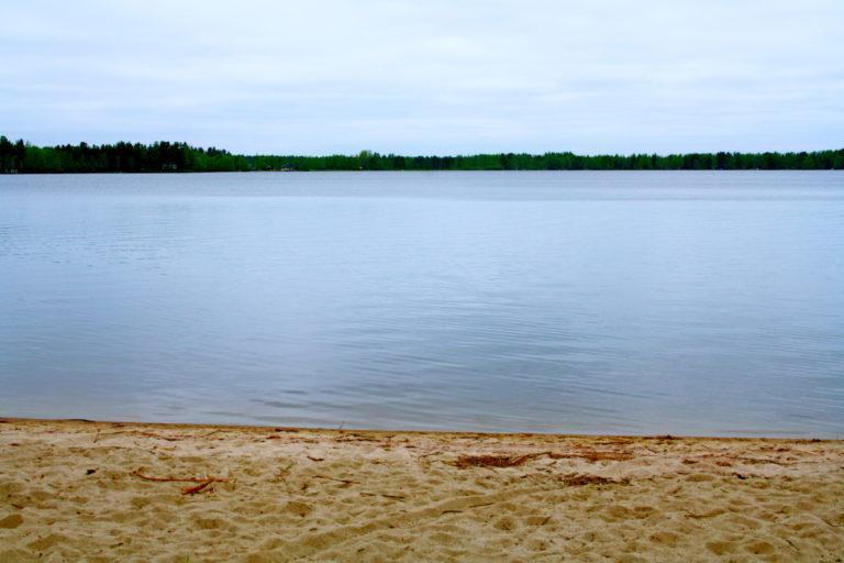 Järvimaisema, etualalla hiekkaa. Pilvinen taivas.