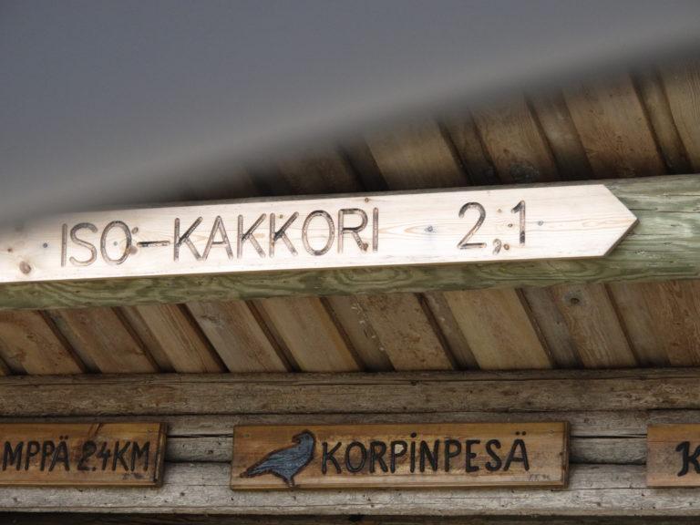 Laavun hirsinen seinä, jossa puiset opaskyltit Iso-Kakkori ja Korpinpesä.