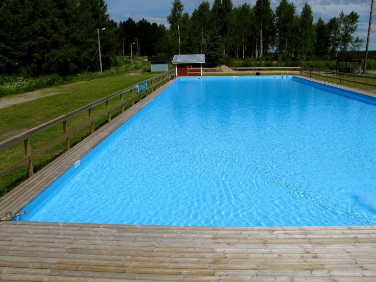 Uimaallas, jossa kirkkaan sininen pohja ja puiset reunat. Taustalla pieni rakennus ja metsä.