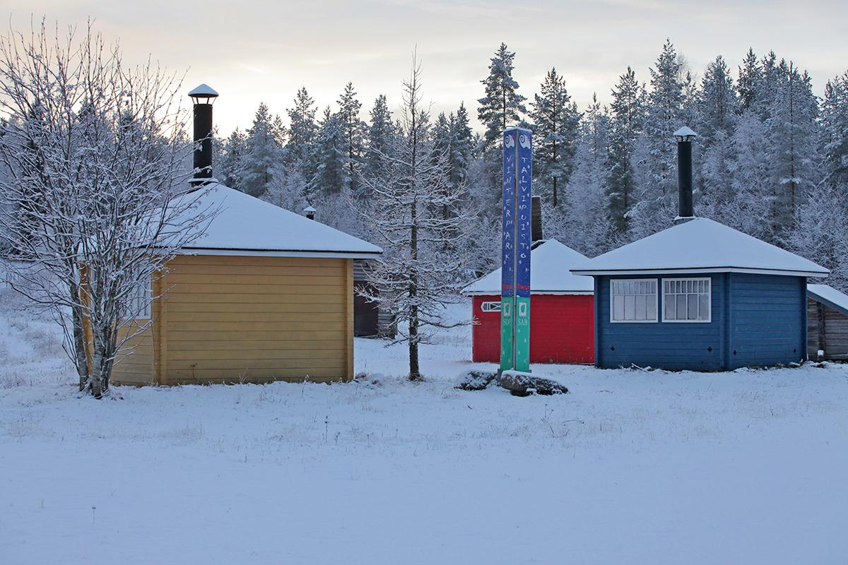 Parran talvipuistossa voit valita neljän eri tulipaikan välillä. Kuvassa keltainen, sininen, punainen ja puun värinen grillikatos sekä Talvipuiston kyltti. Talvinen luminen maisema.