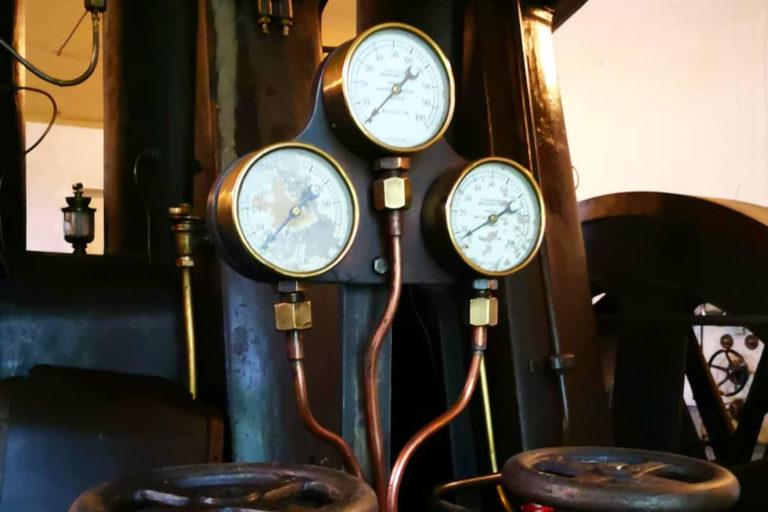 Jyllinkosken sähkömuseon sisältä otettussa kuvassa näkyy kolme mittaria ja kupariputkia.