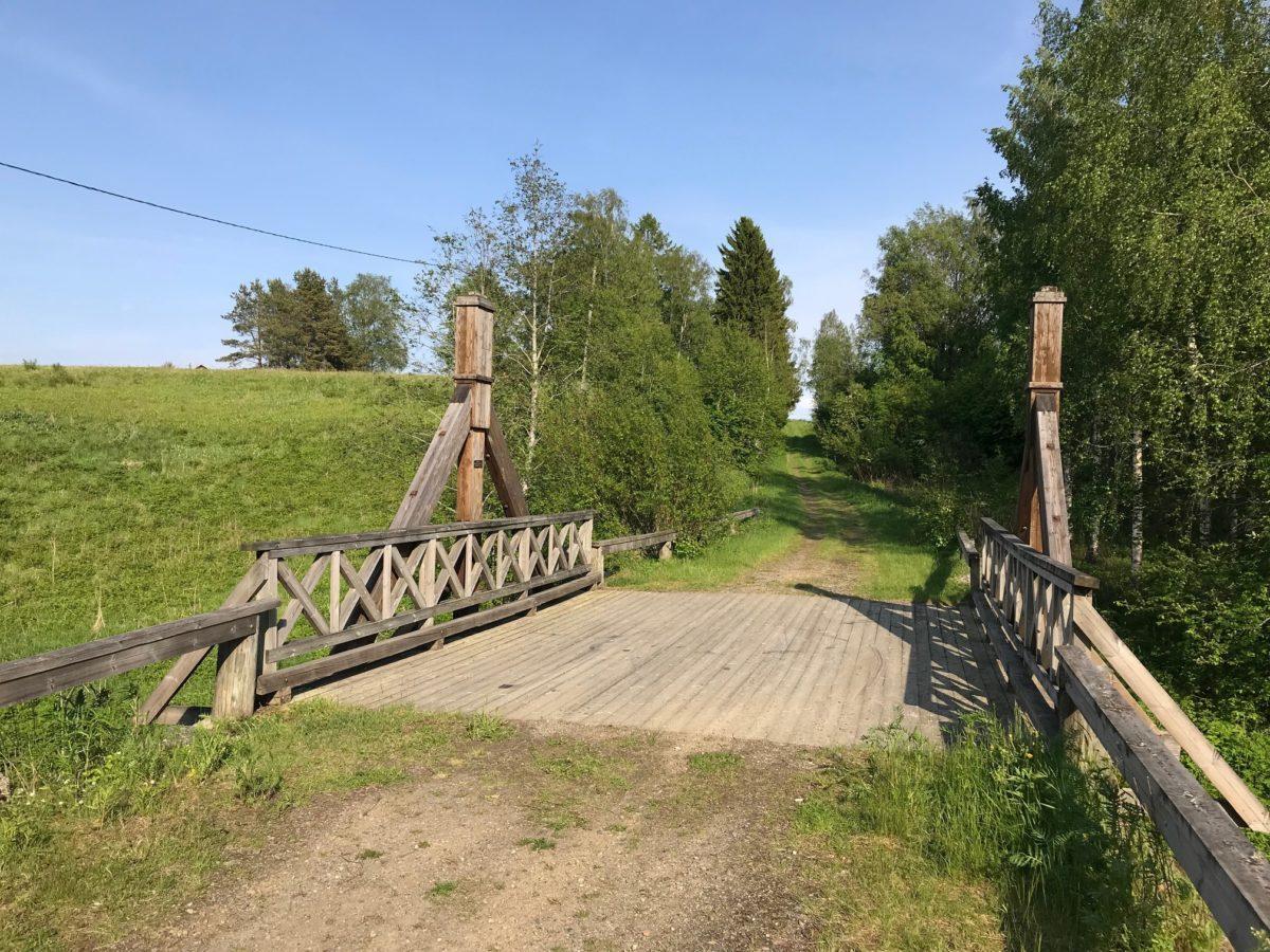 Kivisillan puiset osat sekä sillan yli johtava pieni peltotie. Kesäpäivä, taustalla vihreitä puita ja niitty.