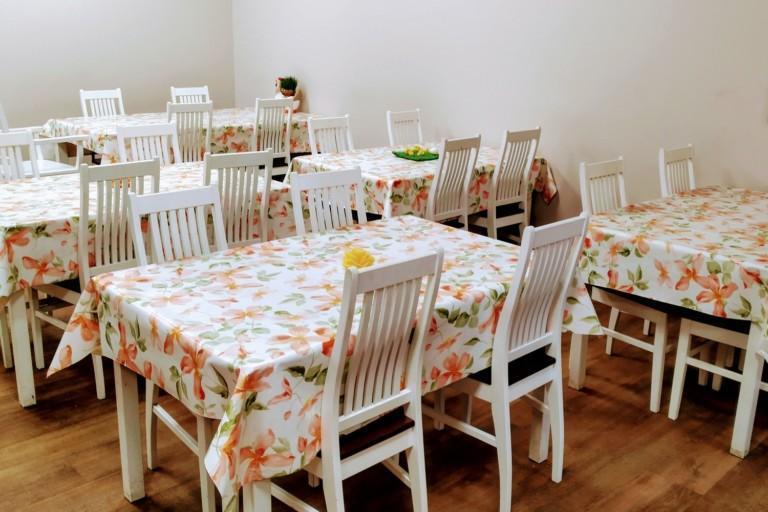 Sisäkuva kahvilasta, kuvassa pöytiä ja tuoleja.