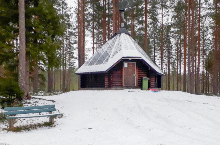 Talvikuvassa keskellä kota, etualalla sininen penkki ja taustalla mäntyjä.