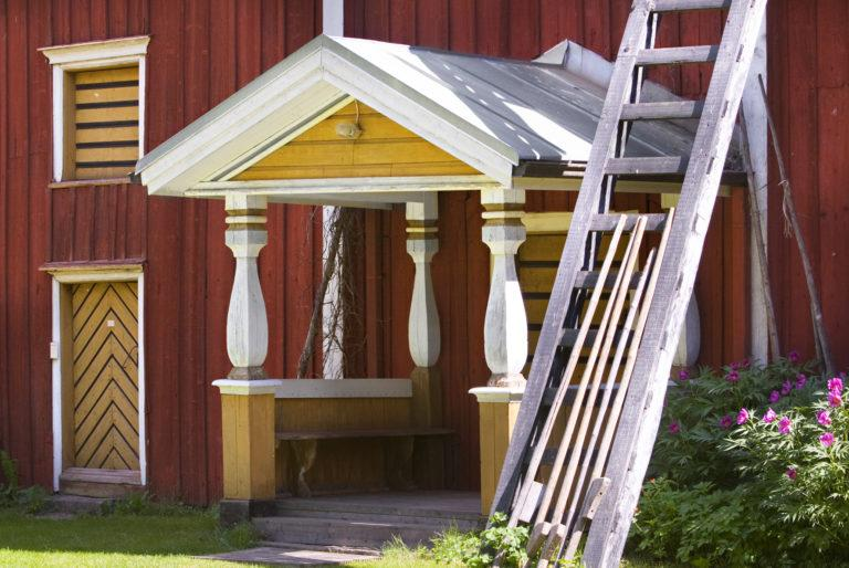 Punaisen rakennuksen kuisti kuvattuna etuviistoon, kuistin vieressä tikapuut.
