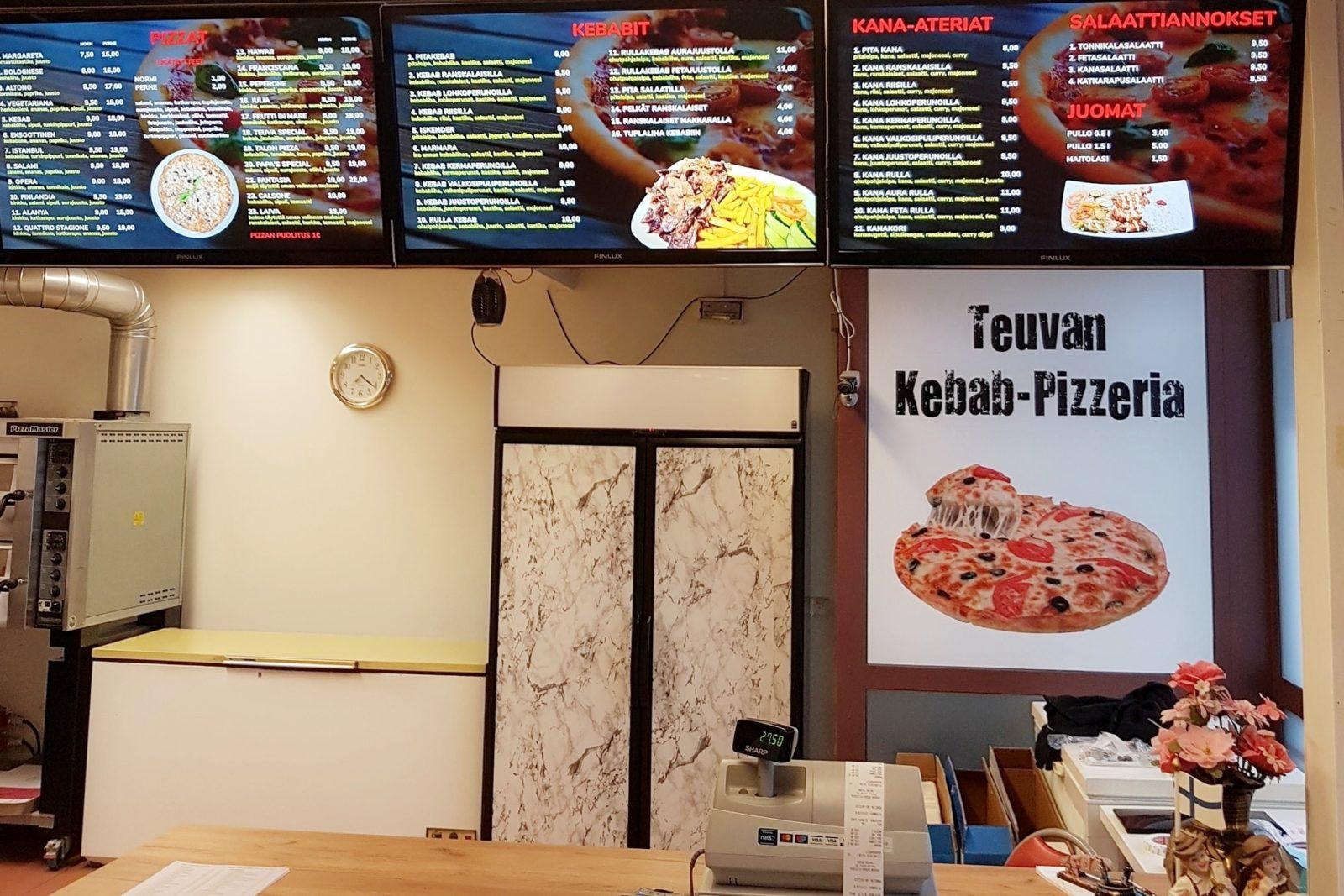Sisäkuva Teuvan kebab-pizzeriasta, kuvassa hinnasto ja myyntitiski.