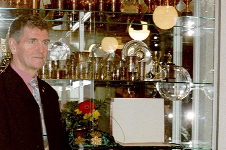 Hiihtäjä Arto koivisto mitalikaapin edessä kuvattuna.