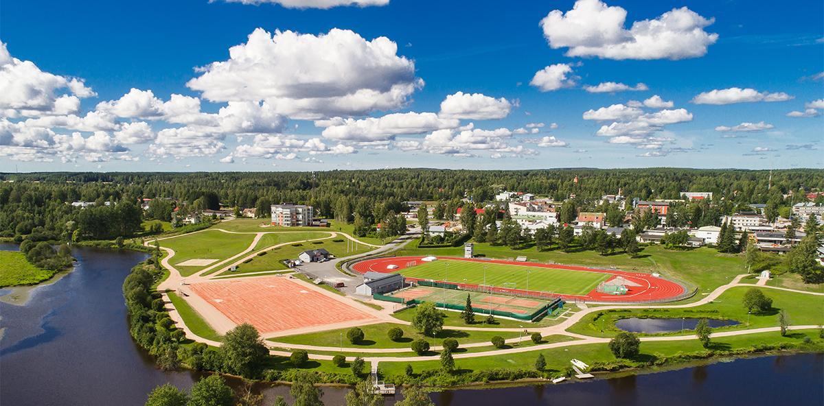Kesäinen ilmakuva Kurikan kaupungista, etualalla joki jonka takana urheilupuisto. Taustalla rakennuksia ja puita, sininen pilvinen taivas.