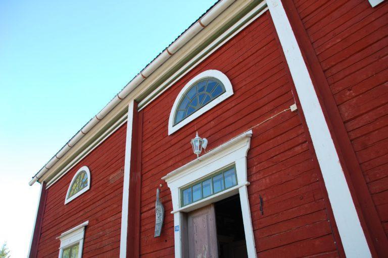 Kurikan museon punainen puurakennuas yläviistoon kuvattuna, sininen taivas.