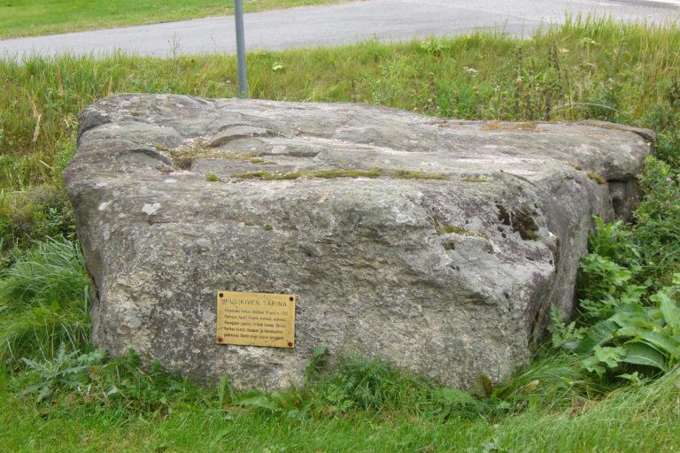 Matala neliskulmainen kivi, jossa kultainen laatta.