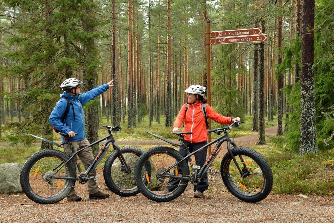 Mies ja nainen seisovat Lauhanvuoren metsässä olevan pyöräilyreitin varrella maastopyöriensä vieressä.