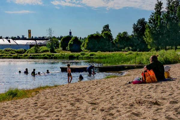 Hiekkarannalla istuu nainen ja vedessä lapsia leikkimässä.