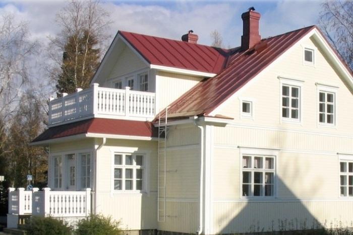 Keltainen punakattoinen kaksikerroksinen talo.