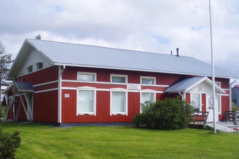Punainen puinen rakennus kuvattu etuviistoon, rakennuksen edessä valkoinen lippusalko.