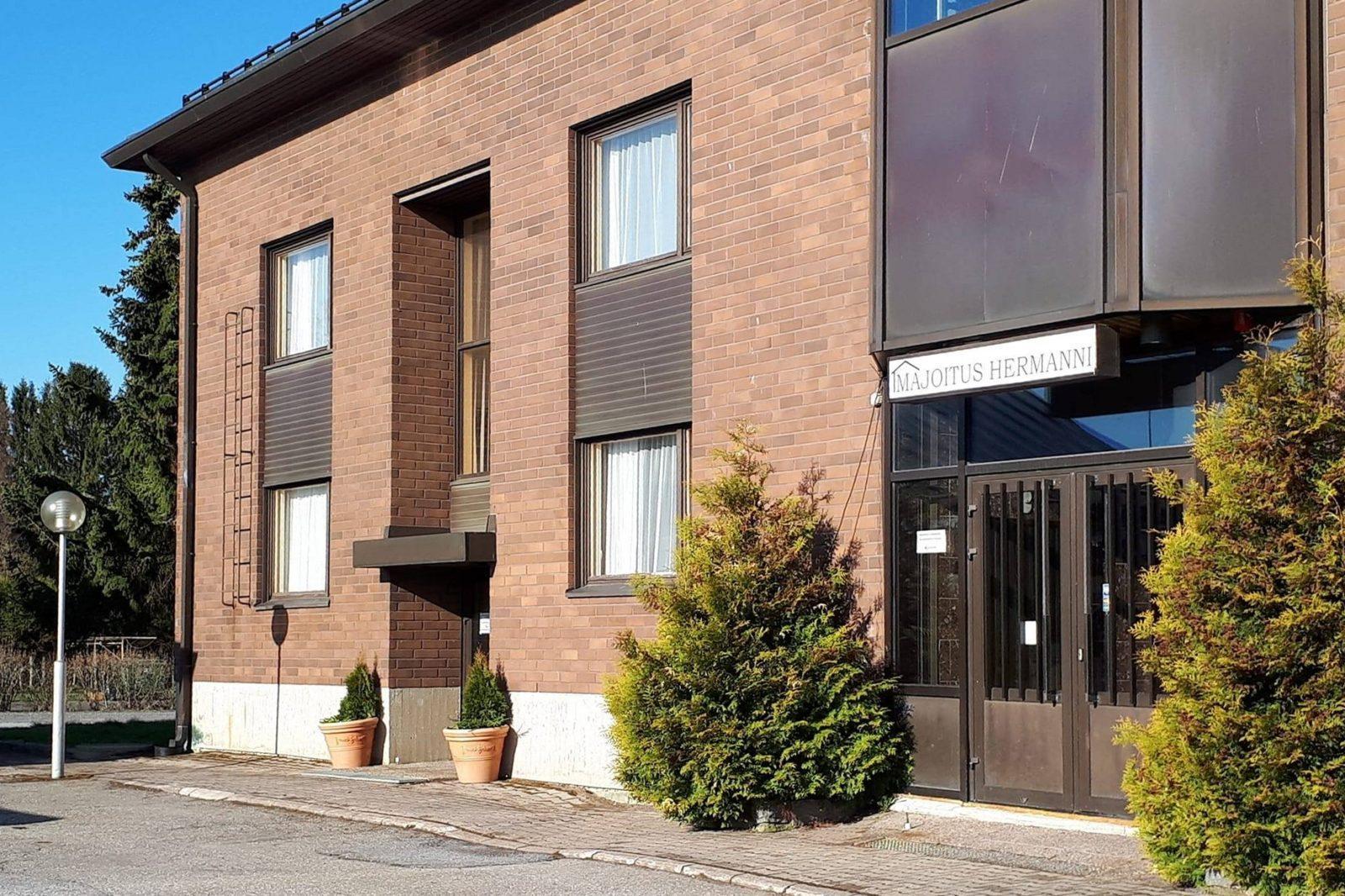 Punatiilinen kaksikerroksinen rakennus kuvattu etuviistoon.