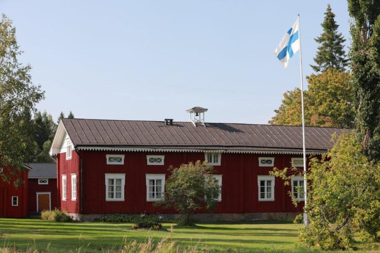 Punainen maalaistalo, etualalla lippusalko, jossa Suomen lippu.